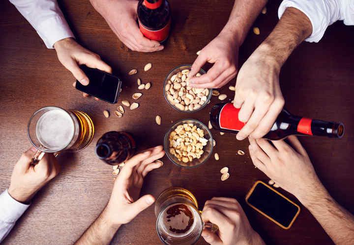 Human hands with beer, telephone, nut