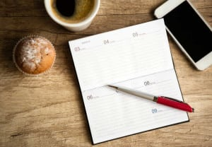 Open notebook on wooden desk, planning workweek