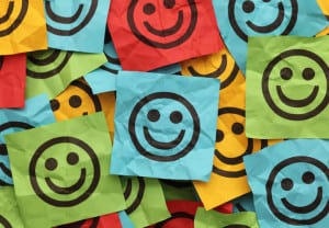 Colorful crumpled adhesive notes with smiling faces.