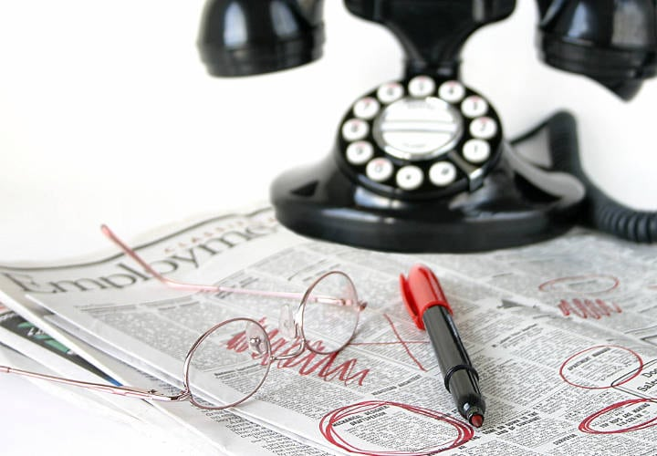un periódico con un teléfono viejo encima y una pluma