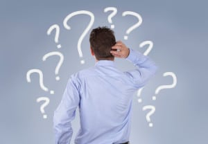 Confused businessman standing in front of a wall of question marks