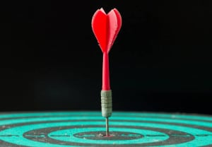 Red dart arrow hitting in the center of green dartboard.