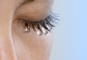 Woman's eye with several teardrops hanging on her eyelashes