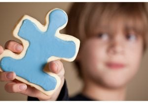 A 9 year old boy holding out a blue iced puzzle piece shaped sugar cookie.  Shallow DOF, focus on cookie only.