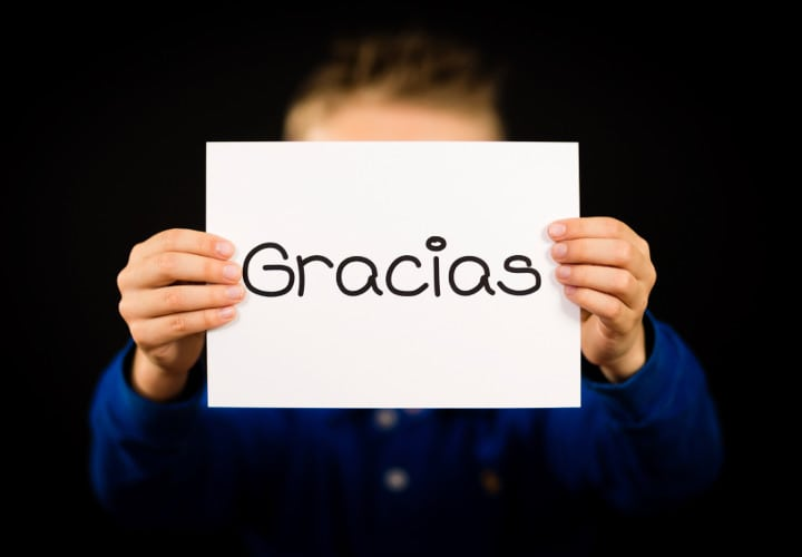 Studio shot of child holding a sign with Spanish word Gracias - Thank You