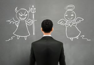 businessman facing of devil and angel over grey wall