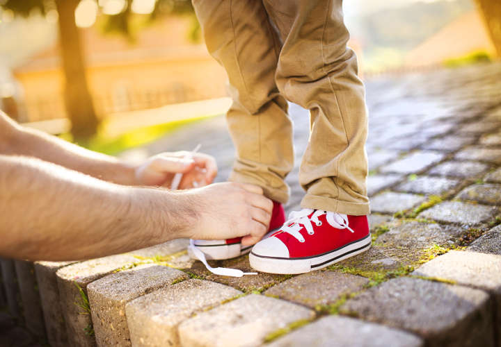 Father tying sons's shoes
