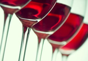 Row of the wine glasses on green light. Selective focus
