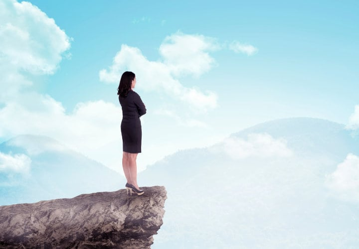 Asian business woman standing on top of the mountain. Business success concept