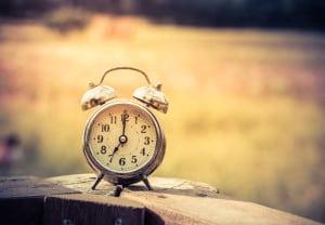 Garden background with retro alarm clock on Wooden