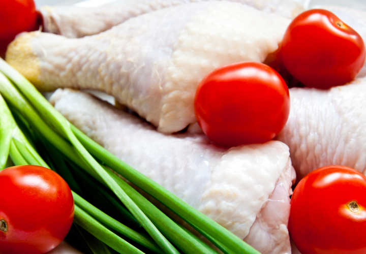 raw chicken with vegetables as a background