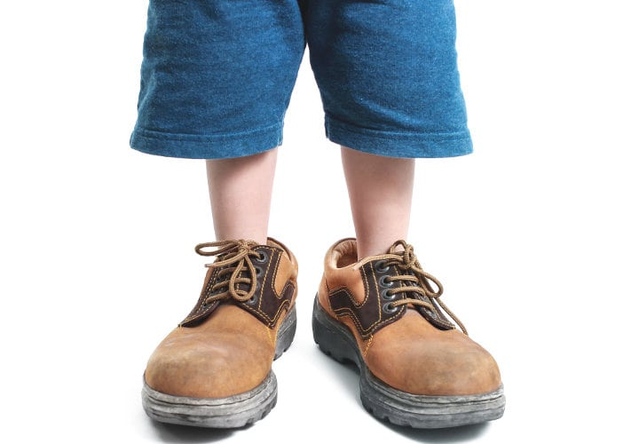 kid in big shoes on white background