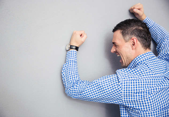 Angry man shouting and hitting gray wall
