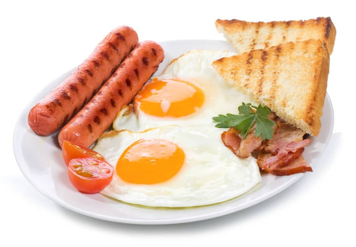 fried eggs with  bacon, sausages and toasts on white background