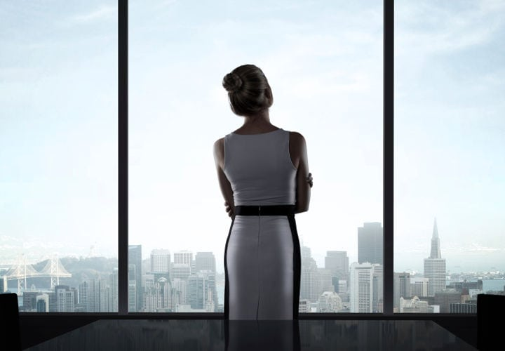 businesswoman standing in office and looking in city