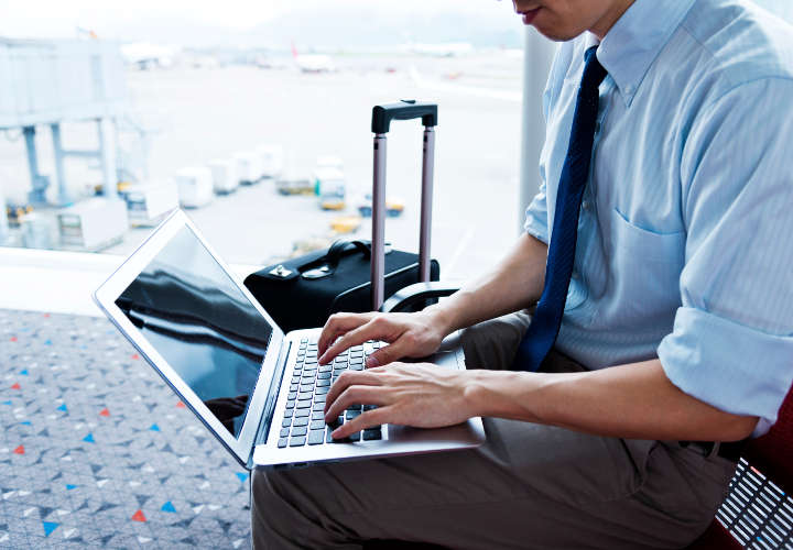 Young businessman working on his laptop in the airport.