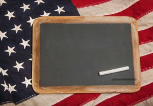 Small chalkboard with a piece of chalk sitting on an American flag