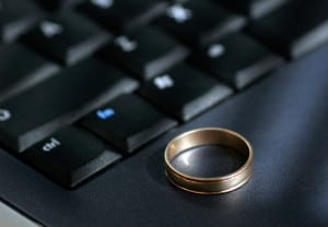 A wedding ring sits on a laptop keyboard