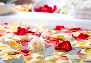 Rose with flower petals in a spa bathtub