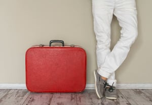 Man stands beside suitcase, home interior