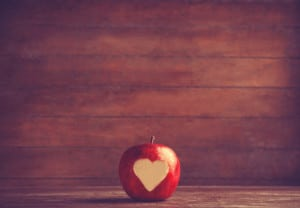 Apple with a heart cut into it. Photo in old color image style.