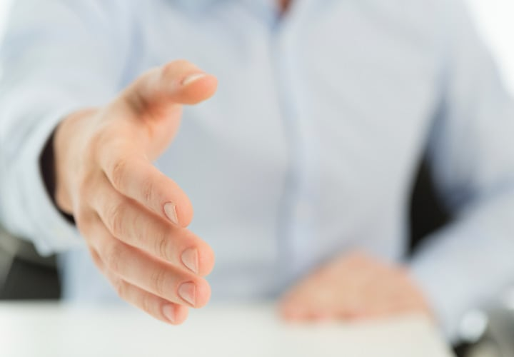 Defocused unrecognizable businessman offering a handshake.