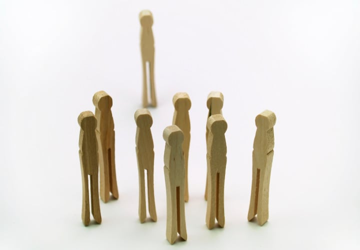 Group of clothespins standing together, one off to itself