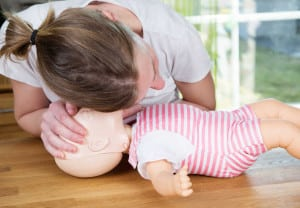 Woman performing CPR on baby training doll, checking for signs of breathing