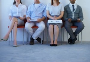 A young woman with a large resume sitting with other prospective employees