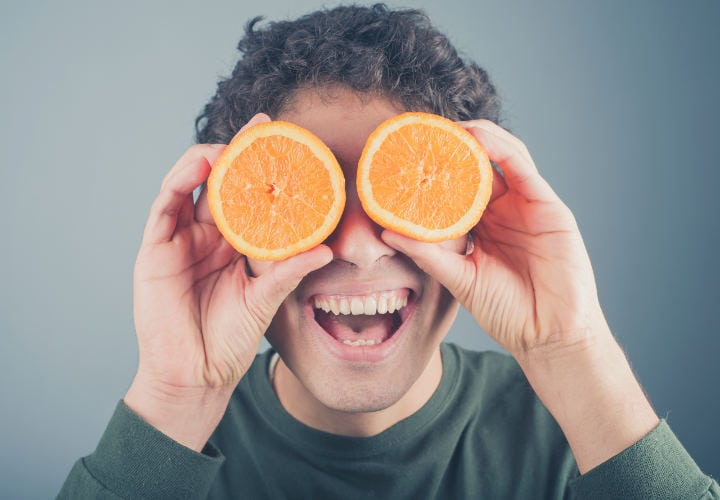 A silly young man is pretending to use two orange halves as binoculars