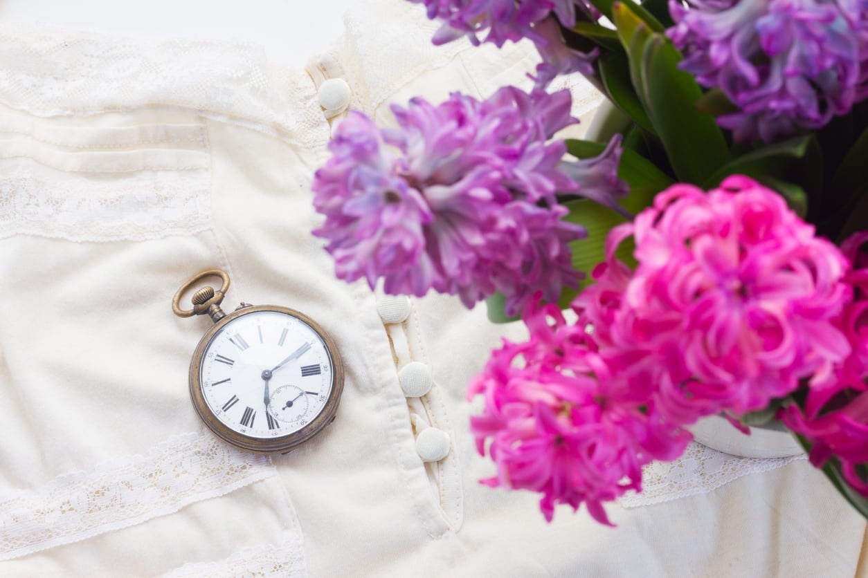 Pink and violet hyacinth flowers with retro dress and antique pocket watch