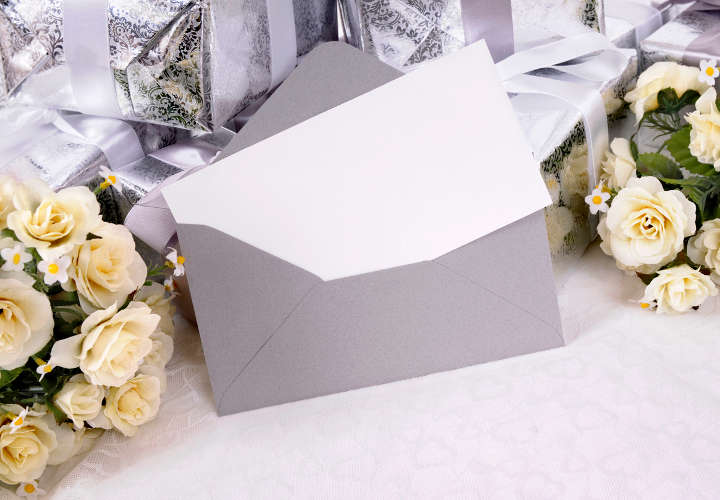 Blank invitation or thank you card with several wedding gifts and white rose fabric bouquet laid on white bridal lace.