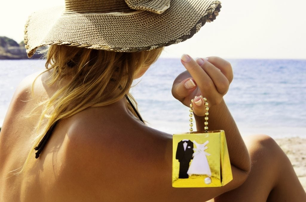 Young woman holding gift box of bride and groom and watching sea on the beach