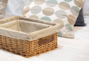 Wicker baskets in different size on a white bed.