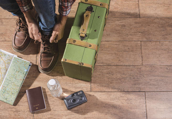 Shoe laces and luggage on wooden floor for travel concept.