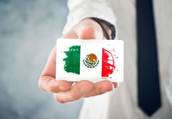 Mexican Businessman holding business card with Mexico Flag. International cooperation, investments, business opportunites concept.