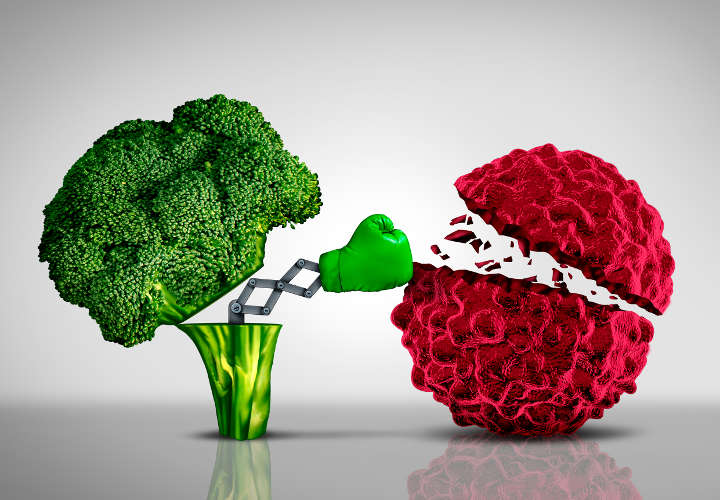 Health food and Cancer fighting foods nutrition concept with a green boxing glove emerging out of an open broccoli vegetable as a health care metaphor for a healthy lifestyle diet rich in natural fruit and vegetables to attack tumors and fight illness.