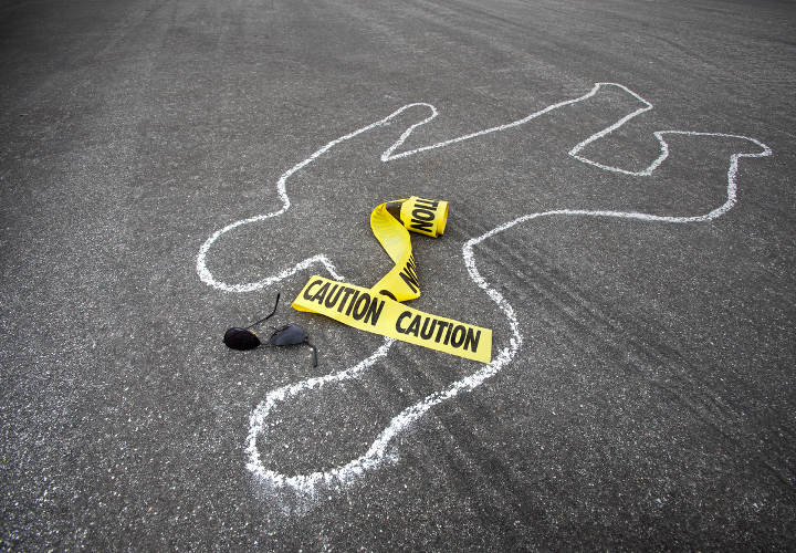 Caution tape and broken sun glasses rest near a chalk line from an auto accident.