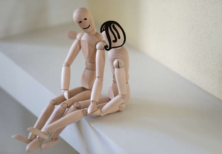 Wooden people sitting at home and hugging. People relationship concept. Drawn faces