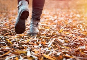 Woman walking over the dry leaves in autumn.