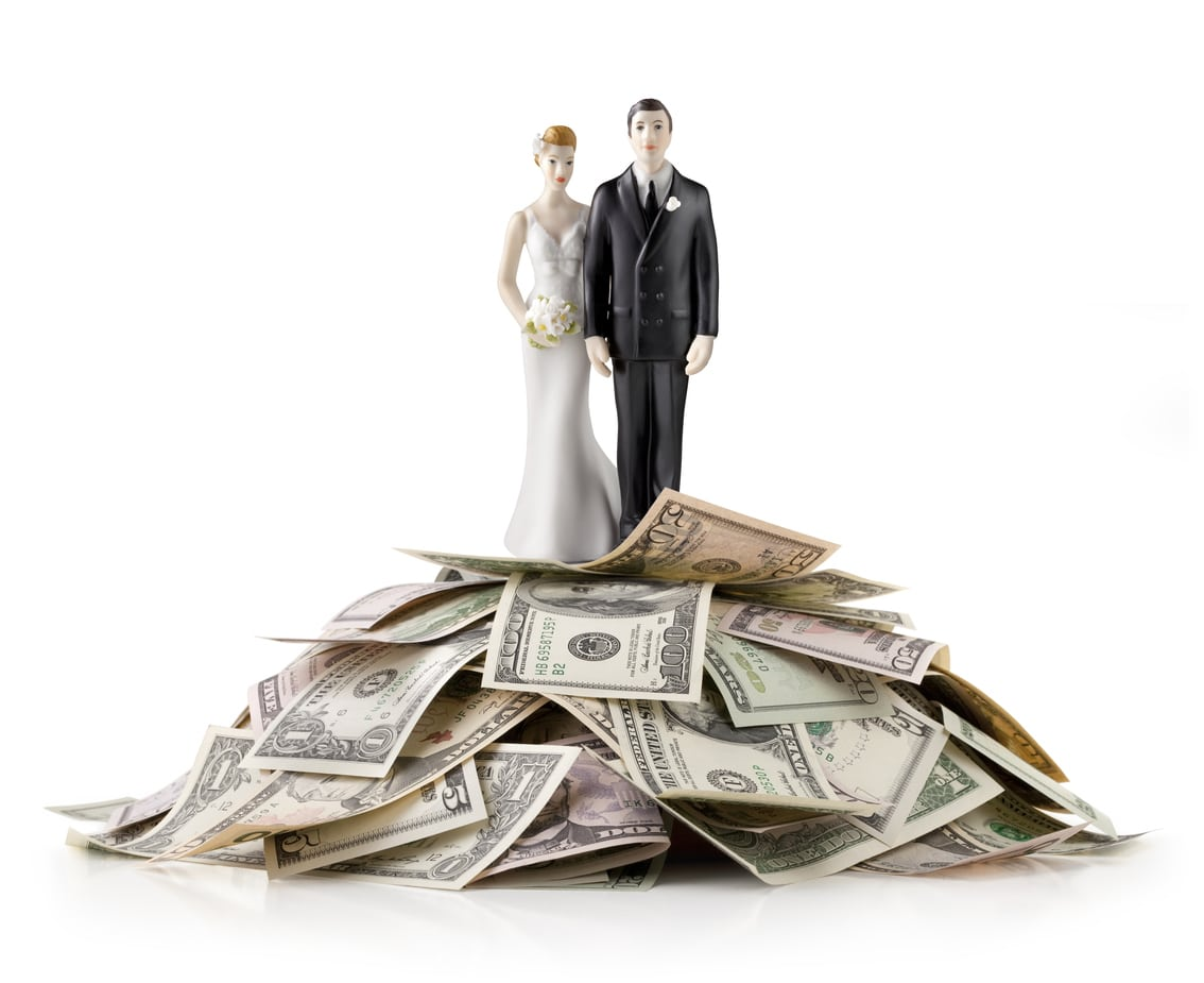 Heap of money with wedding cake topper.