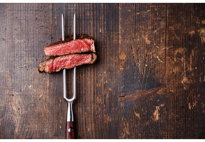 Slices of Medium rare grilled Steak Ribeye on meat fork on dark wooden background