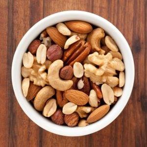 Top view of white bowl full of variety of nuts