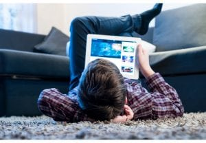 teenager with tablet while lying on the floor in the room
