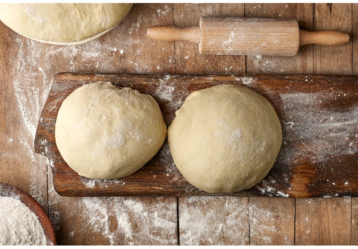 fresh raw dough on rustic wooden table, top view
