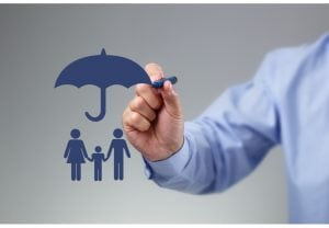 Businessman hand drawing an umbrella above a family concept for protection, security, finance and insurance